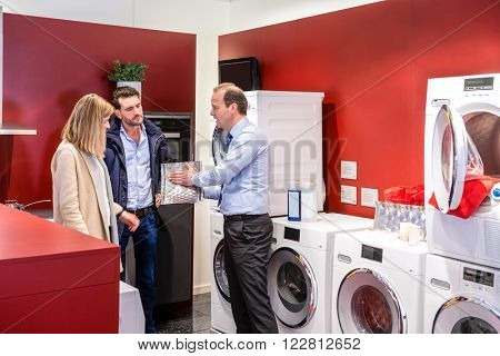Salesman explaining product to couple in washing machine department at electronics shop