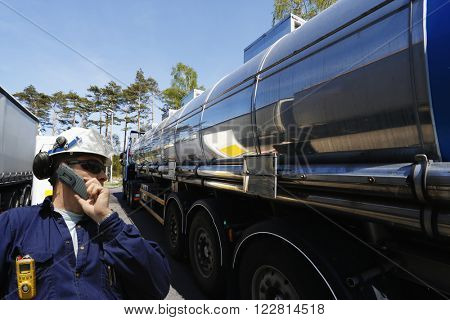 refinery worker filling large fuel-truck inside refinery, oil and gas transportation