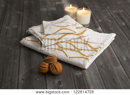 Towels With Orange Concave Lines Alongside Candles And Dried  Citrus