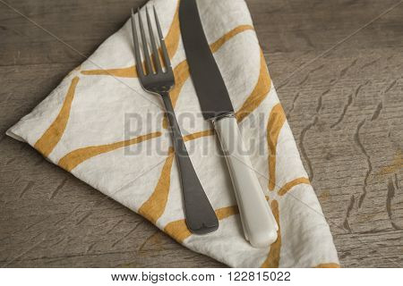 Fork And Knife On White Napkin With Orange Concave Lines