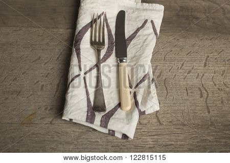Utensils On Napkin With Brown Concave Lines At High Angle