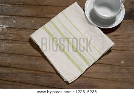 White Dinner Napkin With Green Bands Design Alongside Empty Teacup