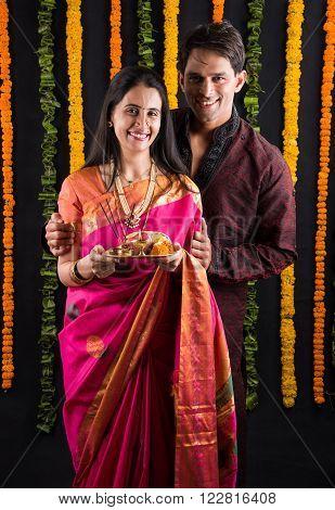 Portrait of Maharashtrian couple holding a puja thali, indian couple holding puja thali or pooja thali, indian couple celebrating diwali, laxmi pujan, asian couple and puja thali, couple doing prayer