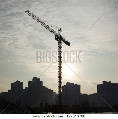Tower crane in the construction site against the sunlight and high-rise city buildings.