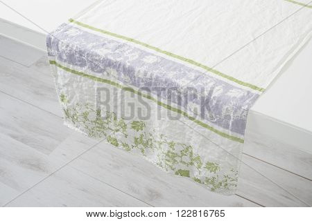 White Hand Towel With Green Floral Accents Over White Counter