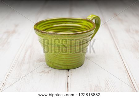 Green Teacup On A White Wooden Panel Surface