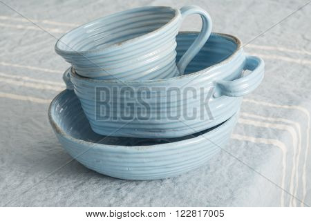 A Stack Of Blue Earthenware On Blue Linen