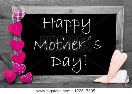 Chalkboard With English Text Happy Mothers Day And Pink Hearts. Wooden Background With Vintage, Rustic Or Retro Style. Black And White Image With Colored Hot Spots.