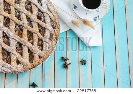 Baked homemade rustic style tart pie with apple jam in ceramic dish next to a cup of coffee, white napkin and star anice over wooden turquoise table background top view, copy space for text