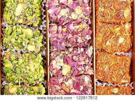 Arabic sweets with rose leaves and pistachios , close up shot