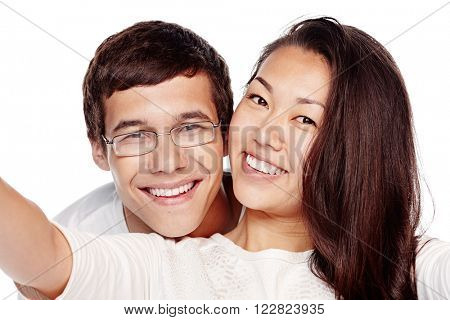 Close up portrait of young interracial couple, hispanic man and asian girl, hugging, smiling attractive healthy toothy smile and taking selfie isolated on white background - dental care concept