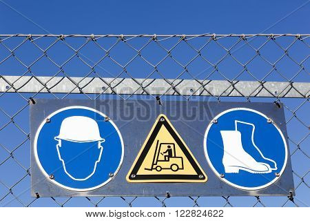 Safety signs on a panel at the entrance of an industrial site