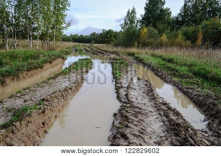 Dirt road in the country flooded with muddy water after rain
