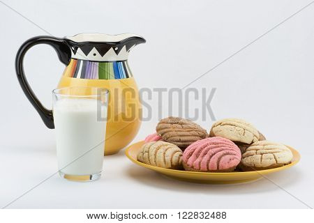 A glass of milk, a pitcher and a plate of concha bread.