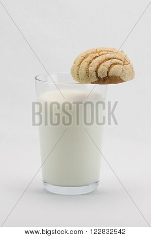 A glass of milk with a concha bread on its rim.