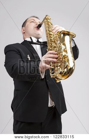Music Themes and Ideas. One Caucasian Male Saxophonist Playing Saxophone in Studio. Against White. Vertical Image