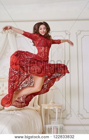 Beautiful woman in a red dress jumping out of bed.