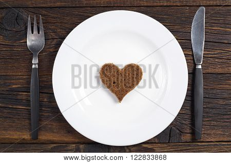 Slice of black bread in the shape of a heart on a plate top view. Next to the plate located cutlery. Conceptual photo.
