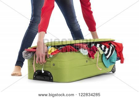 Woman drags the a crowded suitcase on a white background.