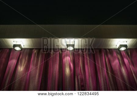 Three included lamps and purple curtains in living room.