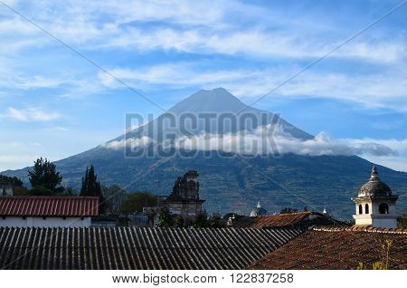 Volcano Agua above the roofs of old quarters of Antigua with clouds resting on it
