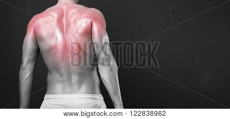 Muscular young man with his back and shoulders inflamed on dark background