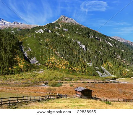 Farmers alpine meadows blocked by low wooden fences. The beautiful autumn day in the Austrian Alps