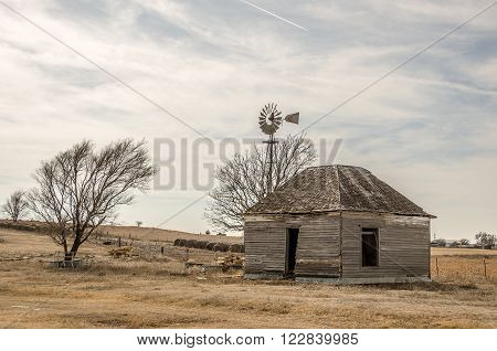 Abandoned home with an old windmill bales of hay and piles of limestone fence posts against a sky of wispy clouds