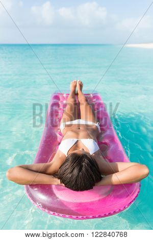 Beach vacation woman relaxing in pink plastic pool toy air bed float floating on ocean water on tropical vacation seen from above lyind down lounging and sunbathing.