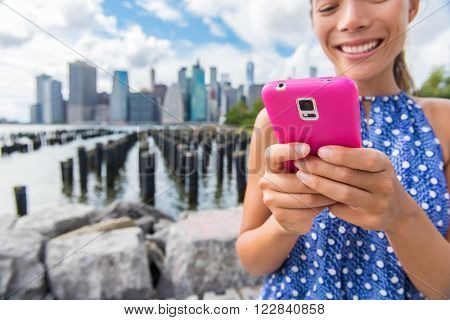 Sms texting phone girl on summer New York travel from Brooklyn Bridge Park Pier 1 view of downtown Manhattan. Closeup of pink smartphone for online social media. Asian woman using technology.