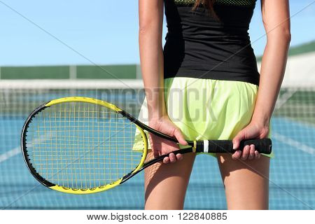 Tennis player holding racket preparing for playing game on outdoor court during summer. Closeup of hands and sport skirt with net in the background. Unrecognizable lower body of person from the back.