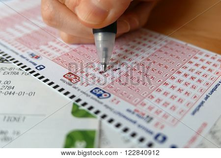 Coquitlam BC, Canada - October 09, 2014 : Close-up of woman hand marking number on 649 lottery ticket