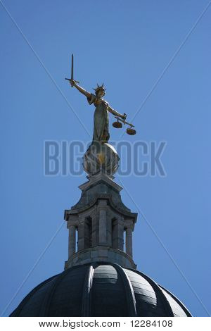 golden statue on top of Old Baily criminal court, London