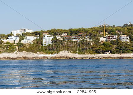 Color DSLR stock image of luxury apartment buildings and condominiums on the rocky Mediterranean coast of the French Riviera. Horizontal with copy space for text ** Note: Visible grain at 100%, best at smaller sizes