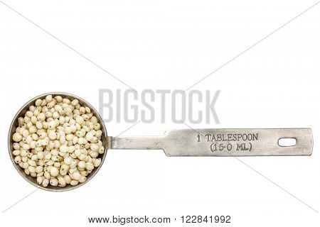 gluten free sorghum grain  in a metal measuring tablespoon isolated on white