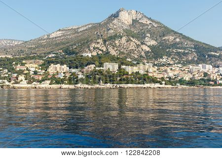 Color DSLR stock image of luxury apartment buildings and condominiums on the rocky, mountainous Mediterranean coast of the French Riviera. Horizontal with copy space for text