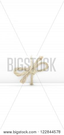 Handmade natural cord bow tied on white message package isolated