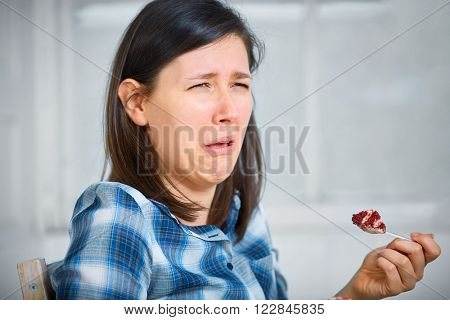 Young disgust female after trying piece of cake, healthy diet concept, avoid sugar