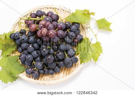 Bunch of grapes and leaves on a bamboo sieve