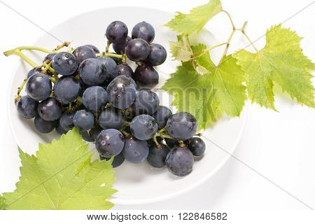 A bunch of grape and leaves on a white plate