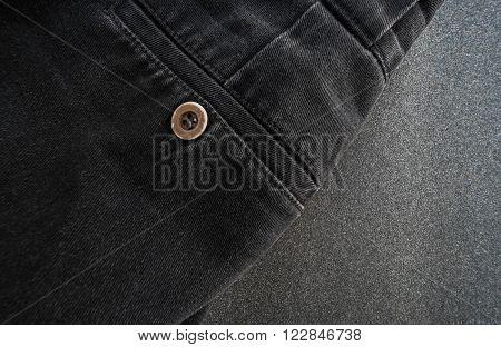 Close up part of black jeans pocket, button focus, on black sandpaper texture background