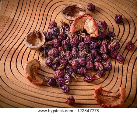 dry rose hips and dried fruit on a wooden board, top view