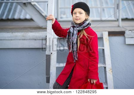 girl in red raincoat on urban metallic stairs