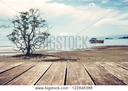 Wooden terrace with the beach, tree and old wooden ship