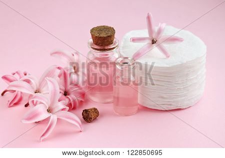 Floral facial tonic in bottles, hyacinth flower scent, cotton pads. Pink background.