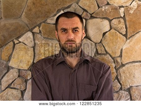 portrait of a sullen unshaven white man in a striped shirt against the wall of stone