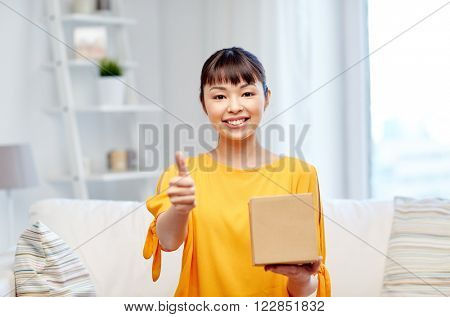 people, delivery, shipping, gesture and shopping concept - happy asian young woman with cardboard parcel box showing thumbs up at home