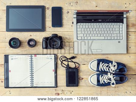 Outfit of a modern photographer, stringer or a news shooter. Set of different objects and equipment: camera, lenses, tablet, phone, usb storage and computer.