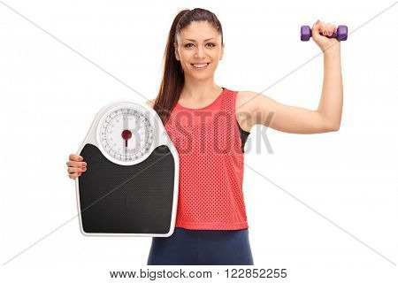Young woman with braces holding a dumbbell and a weigh scale isolated on white background