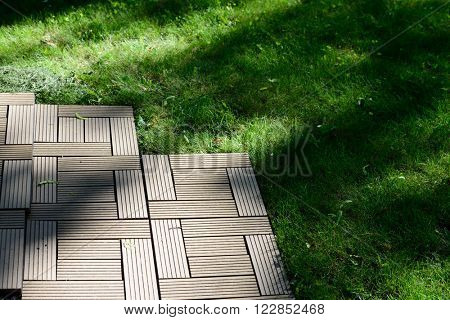 Floor decking on a lawn in a summer day